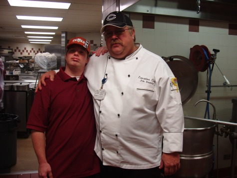 """Dan Riley, shown here with Executive Chef Jim Denvir, volunteers in the kitchen at Little Company of Mary Hospital in Evergreen Park, IL three mornings per week, where he fills the daily """"floor stock"""" food orders for nurses' stations throughout the hospital. """"We appreciate Dan's dependability and enthusiasm and for always doing a great job on the floor stock orders. Dan's attitude contributes to a positive work environment for everyone in the kitchen."""" Jim Denvir Executive Chef Little Company of Mary Hospital"""