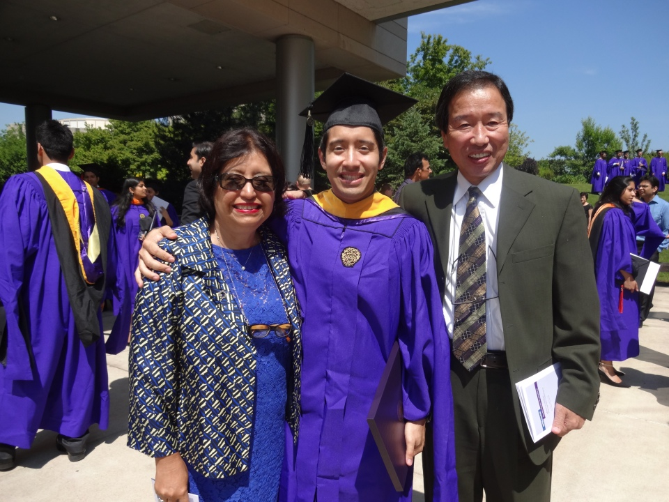 The graduate posing with his parents