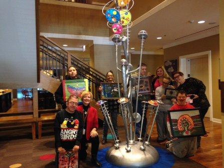 VC14 decorations included Arts of Life paintings shown here with the artists gathered around a fun and unique musical sculpture in the Lurie RMH