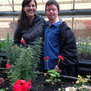 "PHOTO #4 --- Trinity Volunteer Andrew Effgen and Dominican University student Julia Guimond are shown here working in the greenhouse where they are growing herbs in consultation with a local chef who has used these herbs in a cooking demonstration preparing a big Saturday afternoon meal for our Trinity Volunteer Corps to enjoy together at his restaurant which is very appropriately named ""Friendship Chinese Restaurant."""