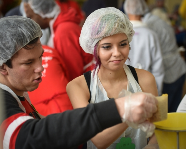 Trinity Volunteer Ian Elsen and Dominican University undergraduate Victoria Lao measure pasta at the beginning of the assembly line.
