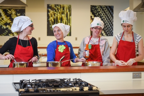 Trinity Volunteer Jackie Finn (second from right) worked in the kitchen with DU Nutrition Science students preparing delicious recipes that augmented the standard macaroni and cheese meals. They fed the packaging volunteers and also printed out the recipes for food pantry volunteers to share with those who will receive the meals.